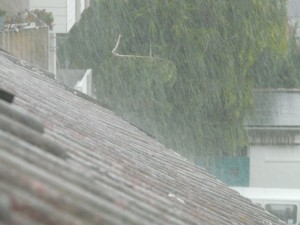 Rain pouring down on a shingled roof